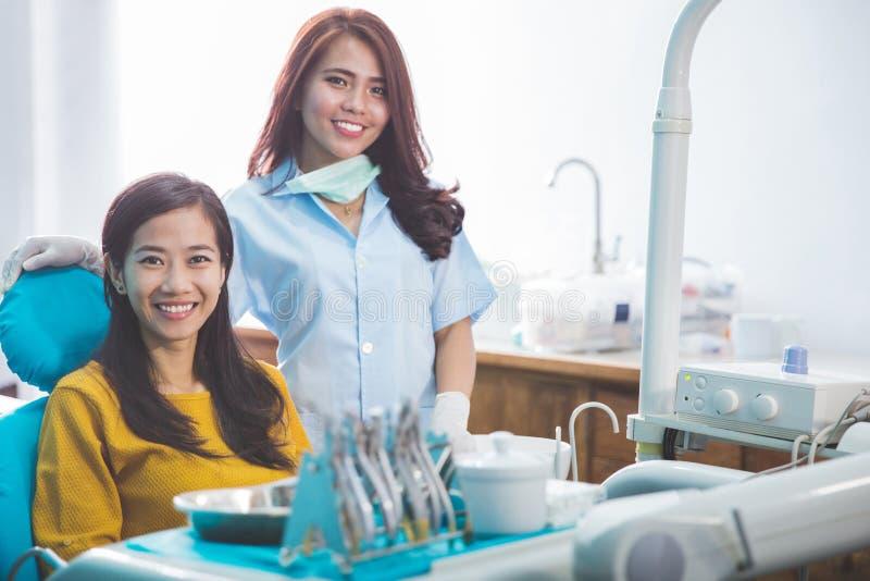 Dentysta ono uśmiecha się z żeńskim pacjentem w stomatologicznej klinice obraz stock
