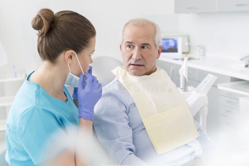 Dentysta opowiada zdziwiony starszy cierpliwy obsiadanie przy stomatologiczną kliniką fotografia stock