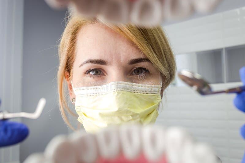 Dentysta patrzeje w zębach nad otwartym cierpliwym ` s usta Oralna opieka zdjęcia stock