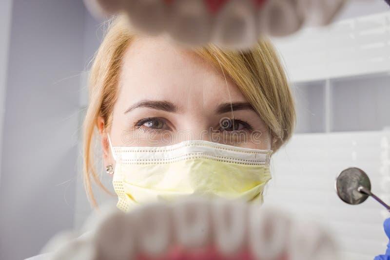 Dentysta patrzeje w zębach nad otwartym cierpliwym ` s usta Oralna opieka Ja obrazy royalty free