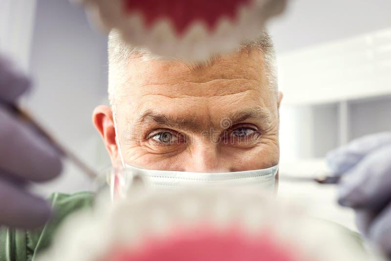 Dentysta patrzeje w zębach nad otwartym cierpliwym ` s usta Oralna opieka Ja fotografia stock