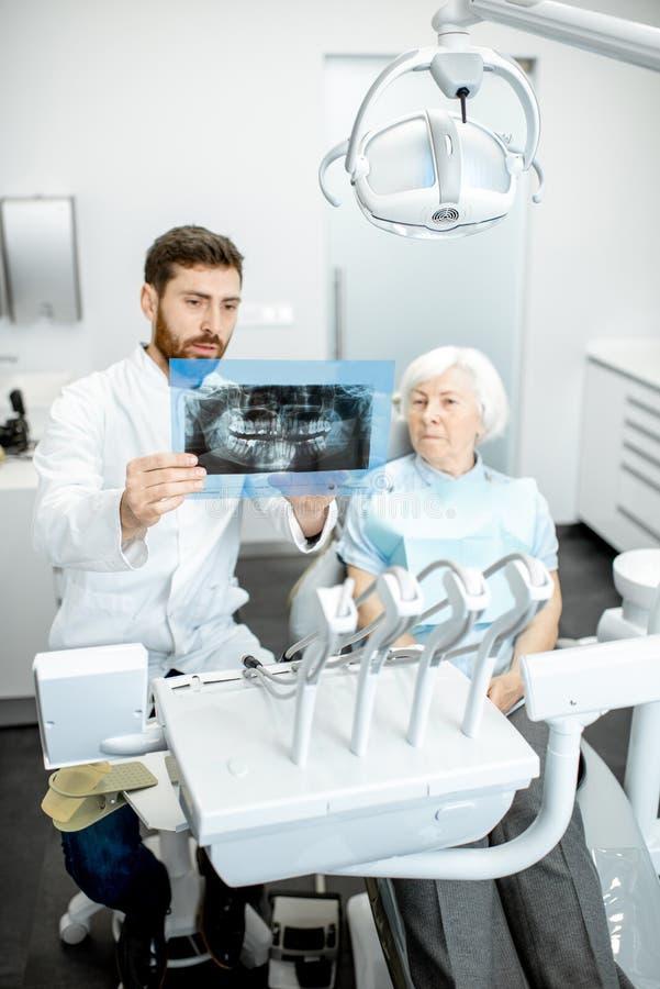 Dentysta pokazuje promieniowanie rentgenowskie stara kobieta w dentall biurze zdjęcia stock