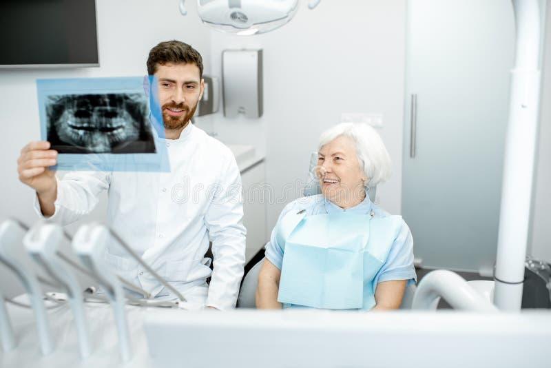 Dentysta pokazuje promieniowanie rentgenowskie stara kobieta w dentall biurze obrazy royalty free