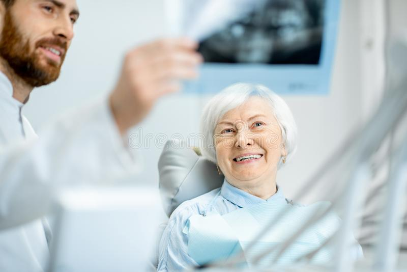 Dentysta pokazuje promieniowanie rentgenowskie stara kobieta w dentall biurze zdjęcie royalty free