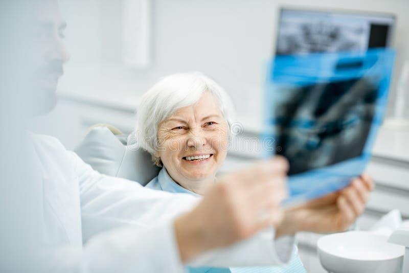 Dentysta pokazuje promieniowanie rentgenowskie stara kobieta w dentall biurze obrazy stock