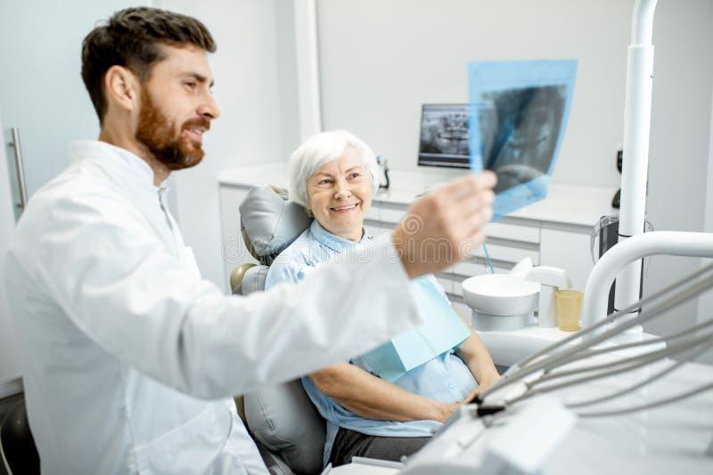 Dentysta pokazuje promieniowanie rentgenowskie stara kobieta w dentall biurze zdjęcie stock