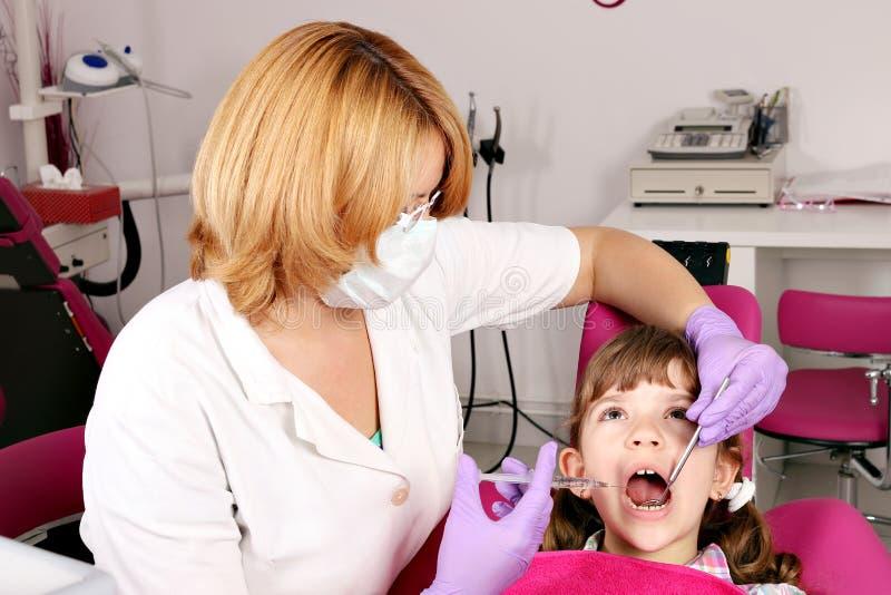 Dentysta taktuje ząb małej dziewczynki fotografia royalty free