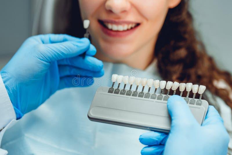 Dentysta wybiera pacjentów zęby barwi z paletą w klinice, zamyka w górę widoku obrazy stock