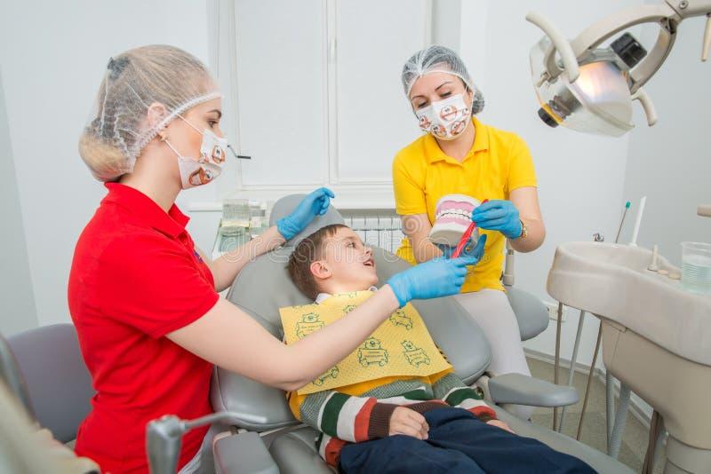 Dentysta z asystentem pokazuje chłopiec dlaczego czyścić zęby z toothbrush na sztucznej szczęki atrapie zdjęcie stock
