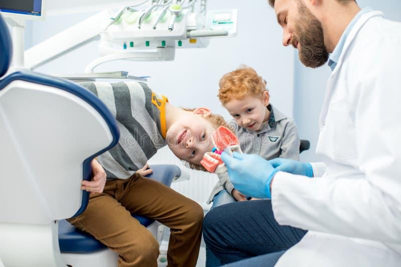 Dentysta z chłopiec przy stomatologicznym biurem zdjęcia stock