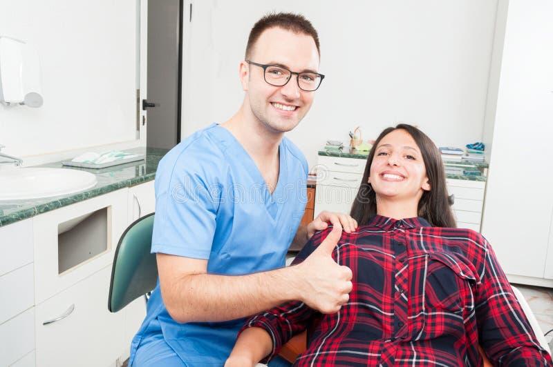 Dentysta z jego cierpliwym ono uśmiecha się pokazuje kciukiem up zdjęcie stock