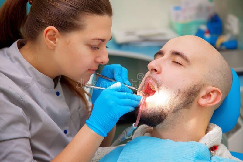 Dentysty egzamininować pod b pacjentów zęby w dentysty krześle obrazy royalty free