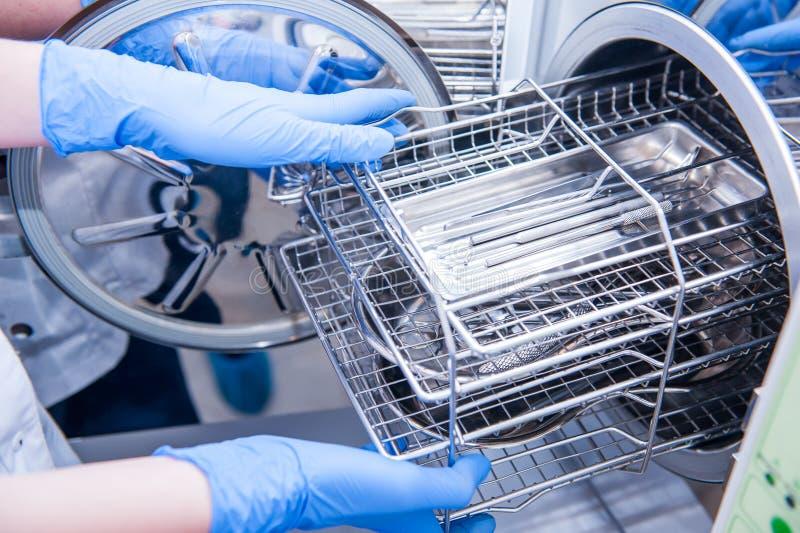 Dentysty ` s pomocnicze ręki wydostawali się sterylizujący medycznych instrumenty od autoklawu Selekcyjna ostrość obrazy royalty free