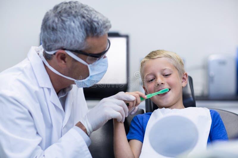 Dentysty szczotkować potomstwo pacjentów zęby fotografia royalty free