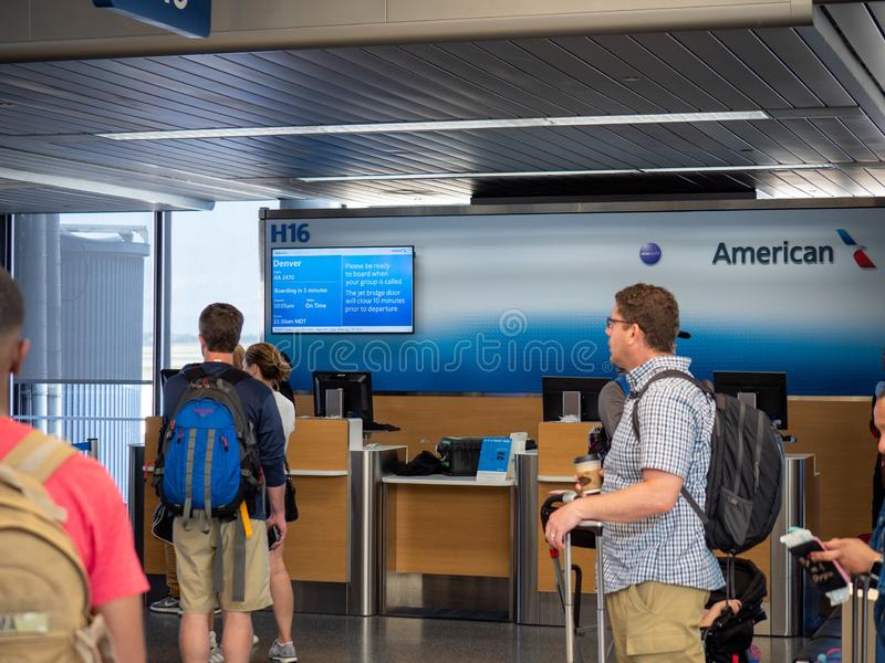 People walk by American Airlines check in help desk at airport royalty free stock image