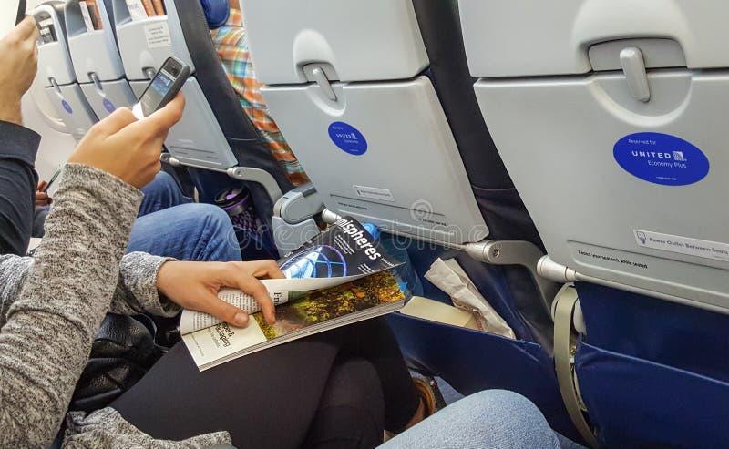 DENVER, Colorado, EUA, o 30 de dezembro de 2017 - uma jovem mulher que usa o App unido em seu smartphone e guardando o compartime foto de stock