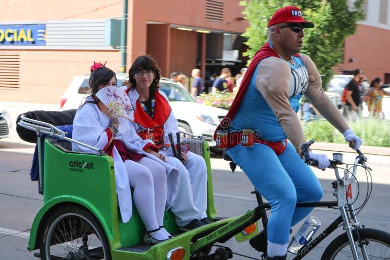 Denver Colorado, USA - Juli 1, 2017: Duffman som kör två geishas i en pedicab på Denver Comic Con fotografering för bildbyråer
