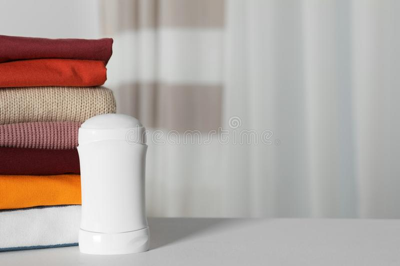 Deodorant near stack of clean clothes on white table. Space for text stock photos
