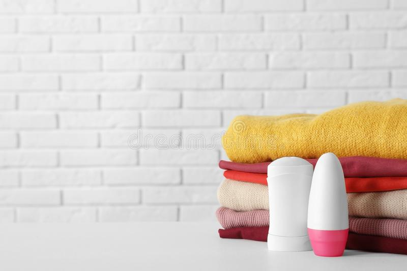 Deodorants near stack of clean clothes on white table. Space for text stock photos