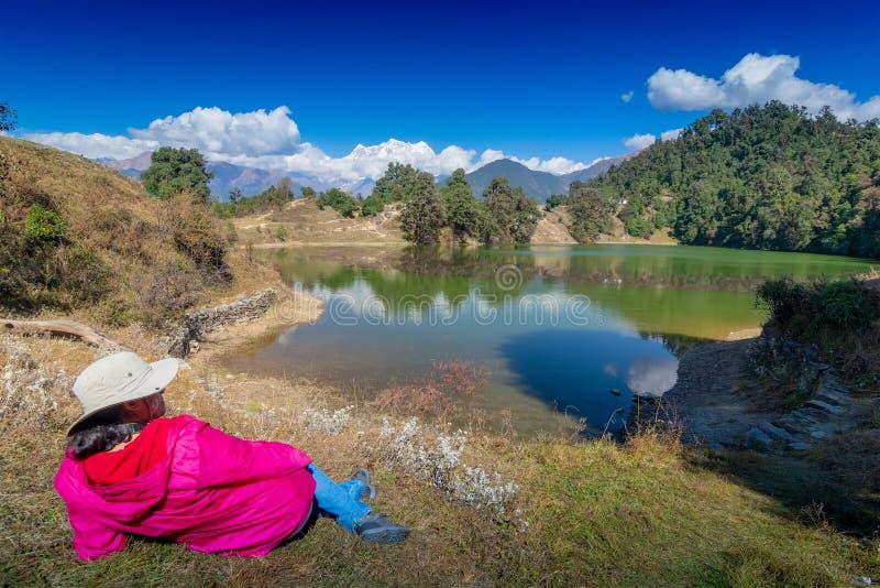 Deoria tal, uttarakhand, India. Solo traveller, single female tourist enjoying beauty of Deoria Tal while lying on green grass, high altitude lake in Uttarakhand stock image