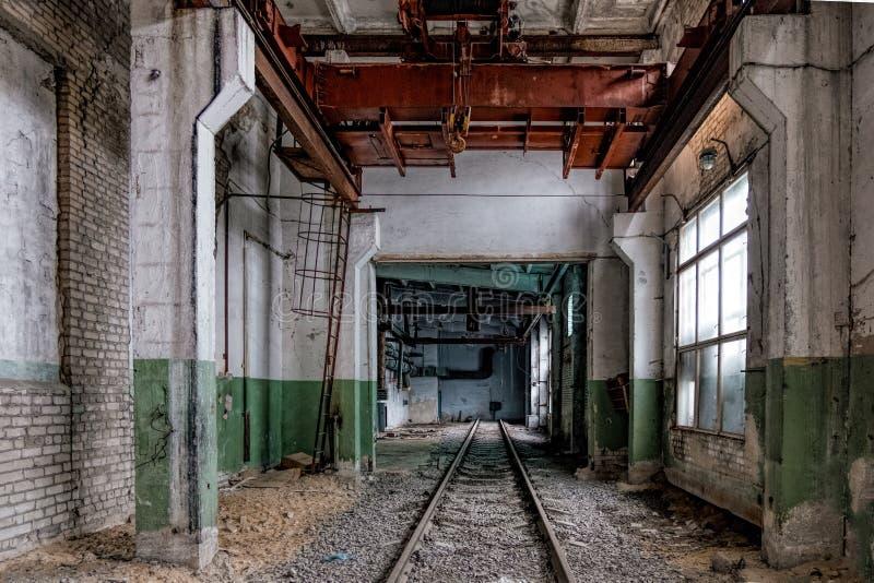 Depósito de trem vazio abandonado com o guindaste de ponte oxidado velho imagem de stock