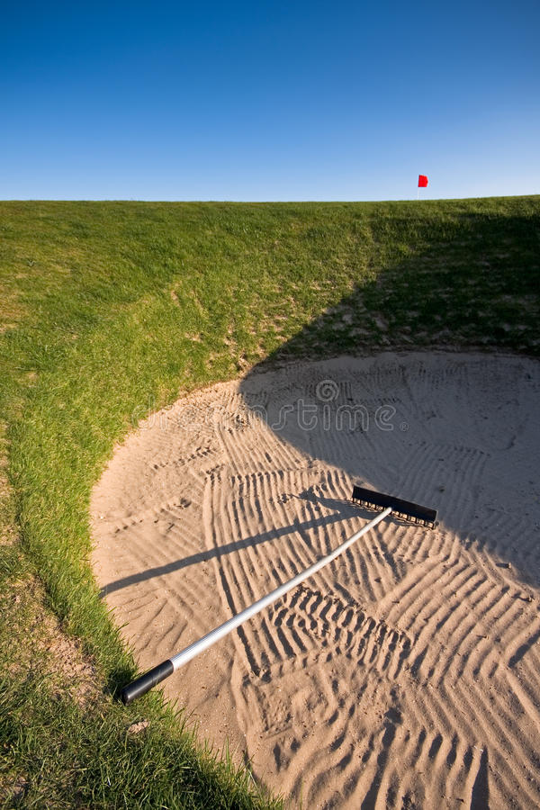 Depósito do golfe com ancinho e a bandeira vermelha fotografia de stock