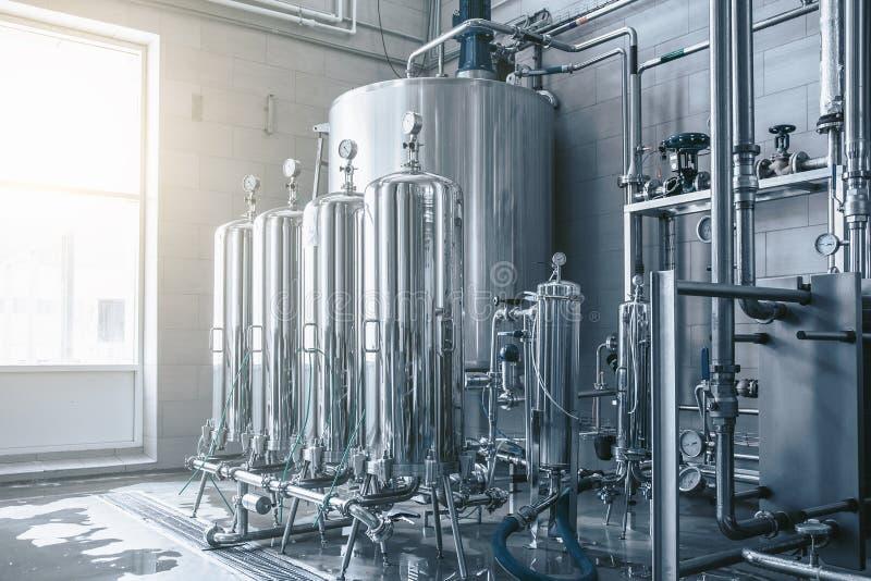 Depósitos y los tanques y tubos grandes en la instalación de producción moderna del jugo y del agua Fondo industrial foto de archivo libre de regalías