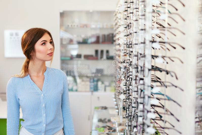 Departamento óptico Mujer cerca del escaparate que busca las lentes fotos de archivo libres de regalías