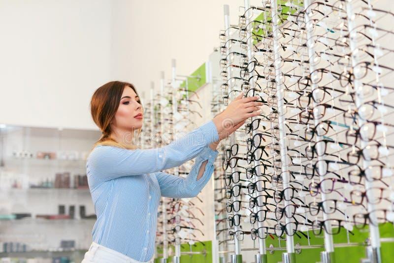 Departamento óptico Mujer cerca del escaparate que busca las lentes imagenes de archivo
