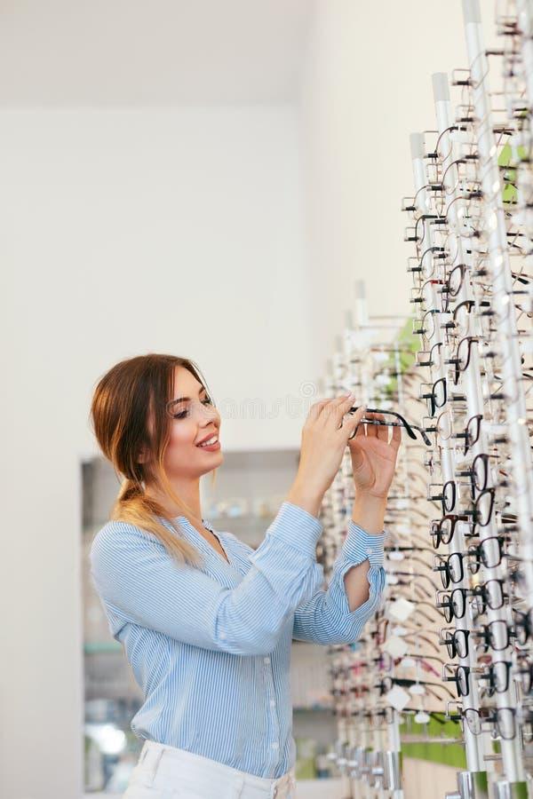 Departamento óptico Mujer cerca del escaparate que busca las lentes fotografía de archivo