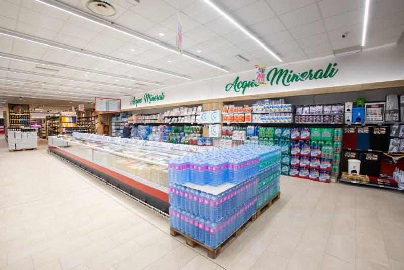 Departamento del agua embotellada, estantes con las diversas botellas plásticas de agua mineral natural y efervescente imagenes de archivo