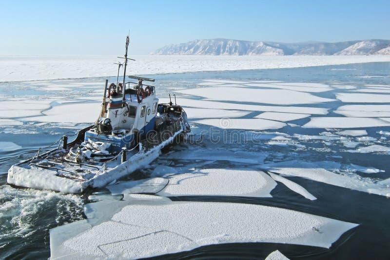 Ship on lake Baikal. Departing ship among the ice floes on lake Baikal in Listvyanka.The mouth of the Angara stock image