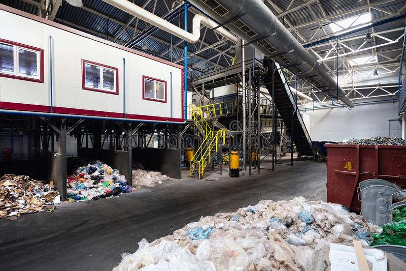 Department of manual waste sorting at modern waste plant with conveyor transports garbage inside drum filter or rotating. Cylindrical sieve with trommel for royalty free stock images