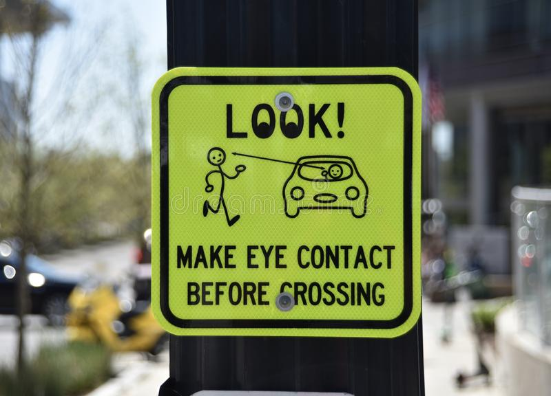 Pedestrian Crosswalk Public Safety Sign. A department of public safety sign at a crosswalk urges pedestrians to make eye contact with moving vehicles before stock photo