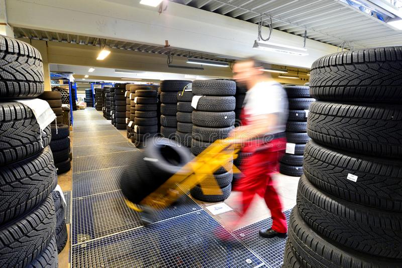 Department store with car tyres in a garage - tyre change. Worker with lifting truck royalty free stock images