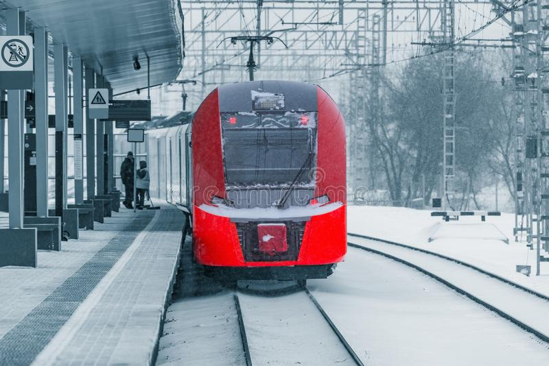 Departure of the highspeed train. Departure of the highspeed train from the station platform at snowstormy day time stock image