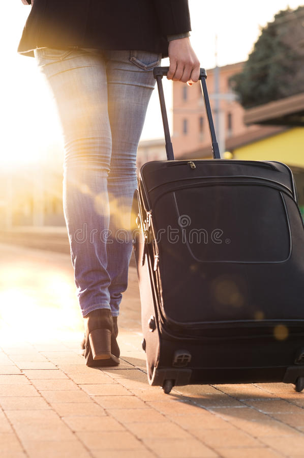 Departure on holidays. Woman wheeling suitcase on railway station platform stock photography