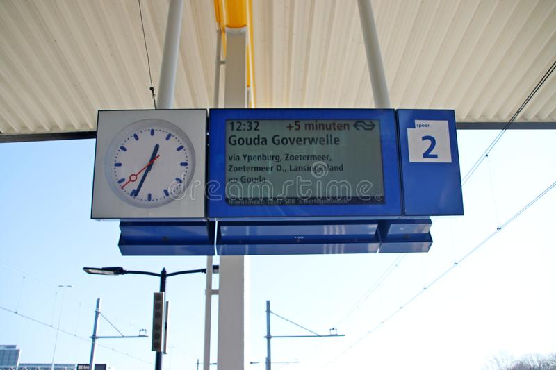 Departure sign on platform with clock with delay information on Voorburg railway station in the Netherlands. royalty free stock photography