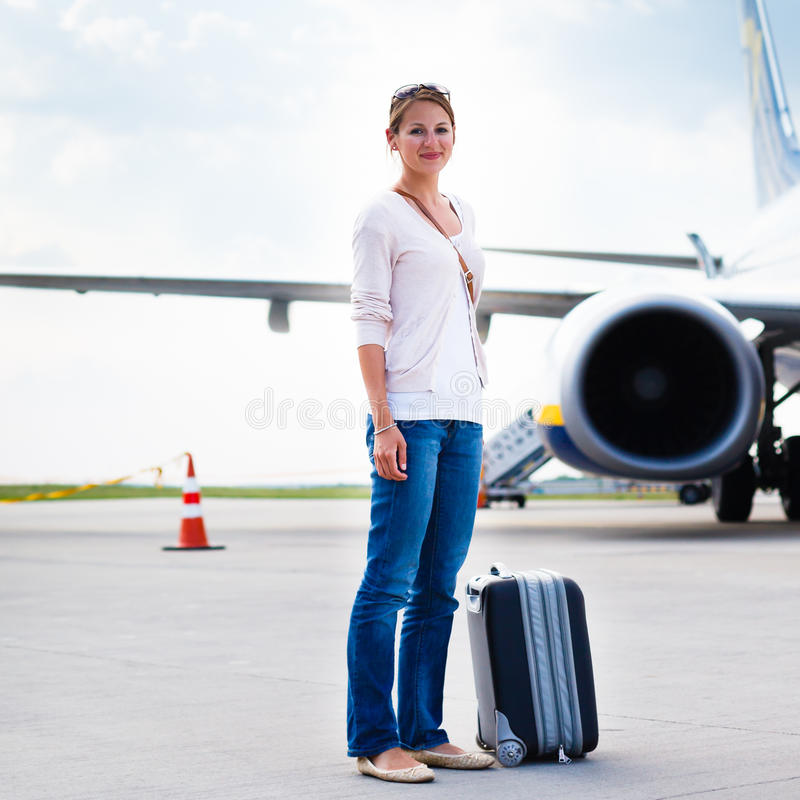 Departure - young woman at an airport. About to board an aircraft on a sunny summer day stock images