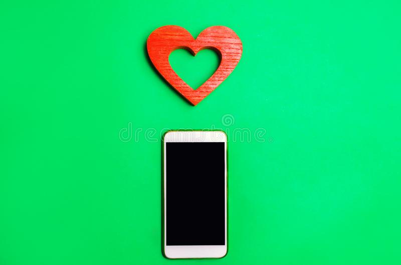 Dependence on social networks. phone smartphone and heart on a green background. online dating, flirting, message and calling your stock photos