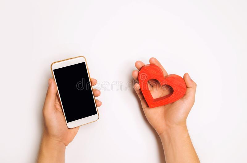 Dependence on social networks. phone smartphone and heart in hands. online dating, flirting, message and calling your loved one. c stock photo