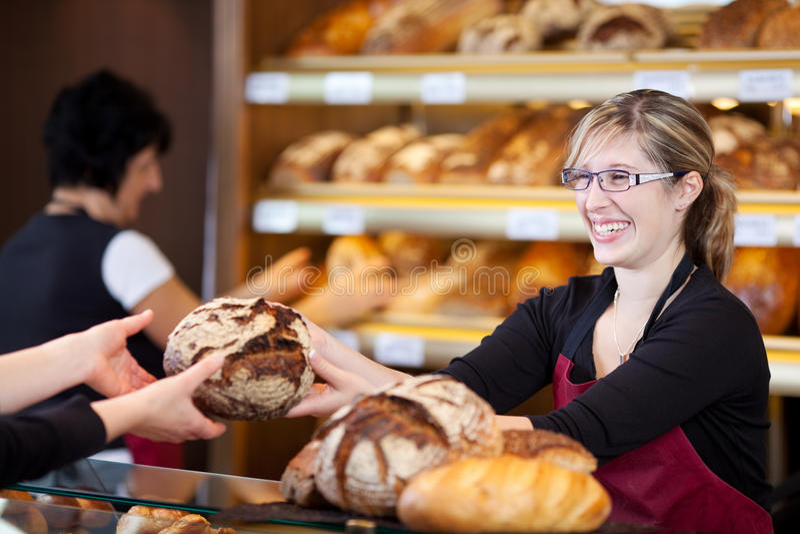 Dependienta amistosa en la panadería que pasa el pan imagen de archivo