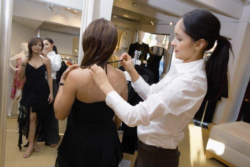 Dependienta Assisting Female Customer con el vestido imagen de archivo