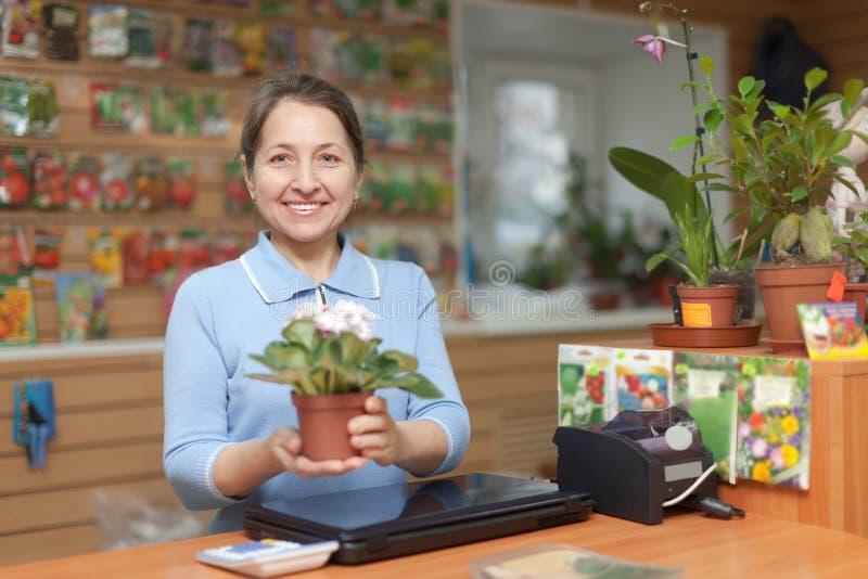 Dependienta con la flor en la tienda del jardín foto de archivo