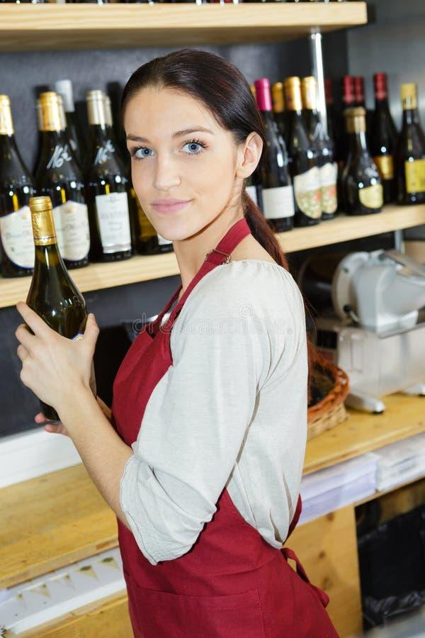Dependienta feliz Standing Against Shelves en tienda de vino imágenes de archivo libres de regalías