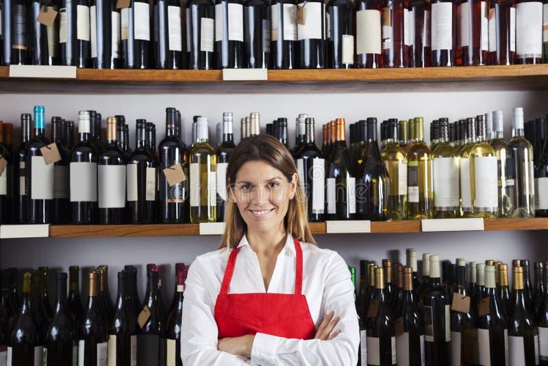 Dependienta feliz Standing Against Shelves en tienda de vino fotografía de archivo