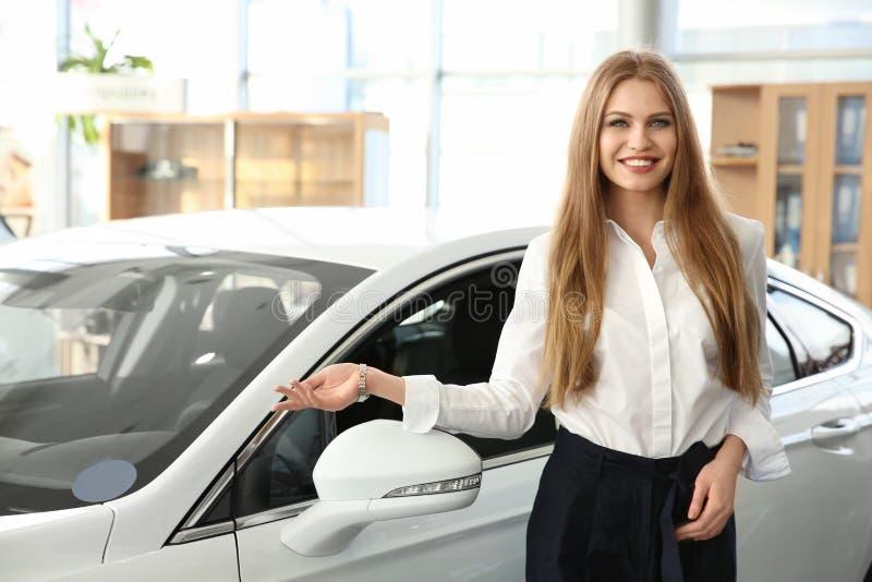 Dependienta joven que se coloca cerca del nuevo coche fotos de archivo
