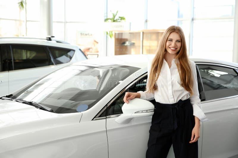 Dependienta joven que se coloca cerca del nuevo coche fotos de archivo libres de regalías