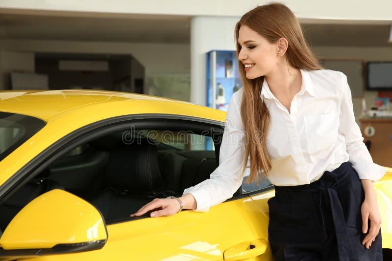 Dependienta joven que se coloca cerca del nuevo coche imagen de archivo