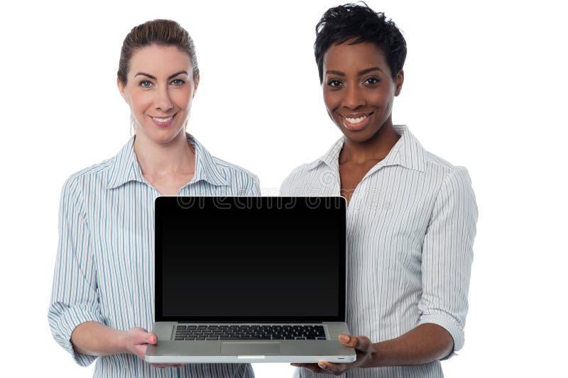 Dependientas que presentan el ordenador portátil a estrenar imagen de archivo
